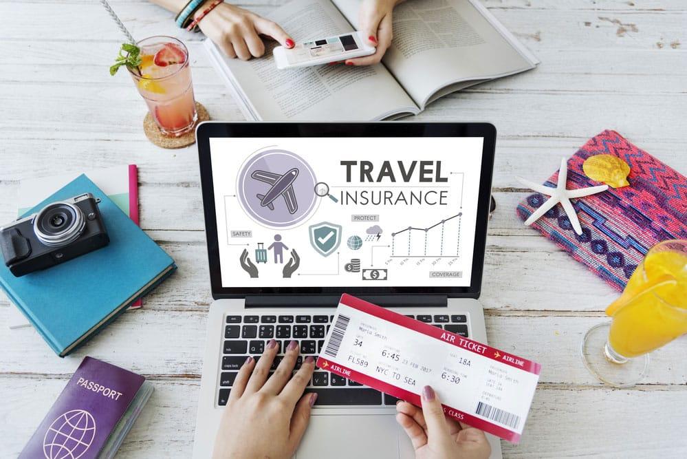 Seguro de viajes en la mano delante de portátil