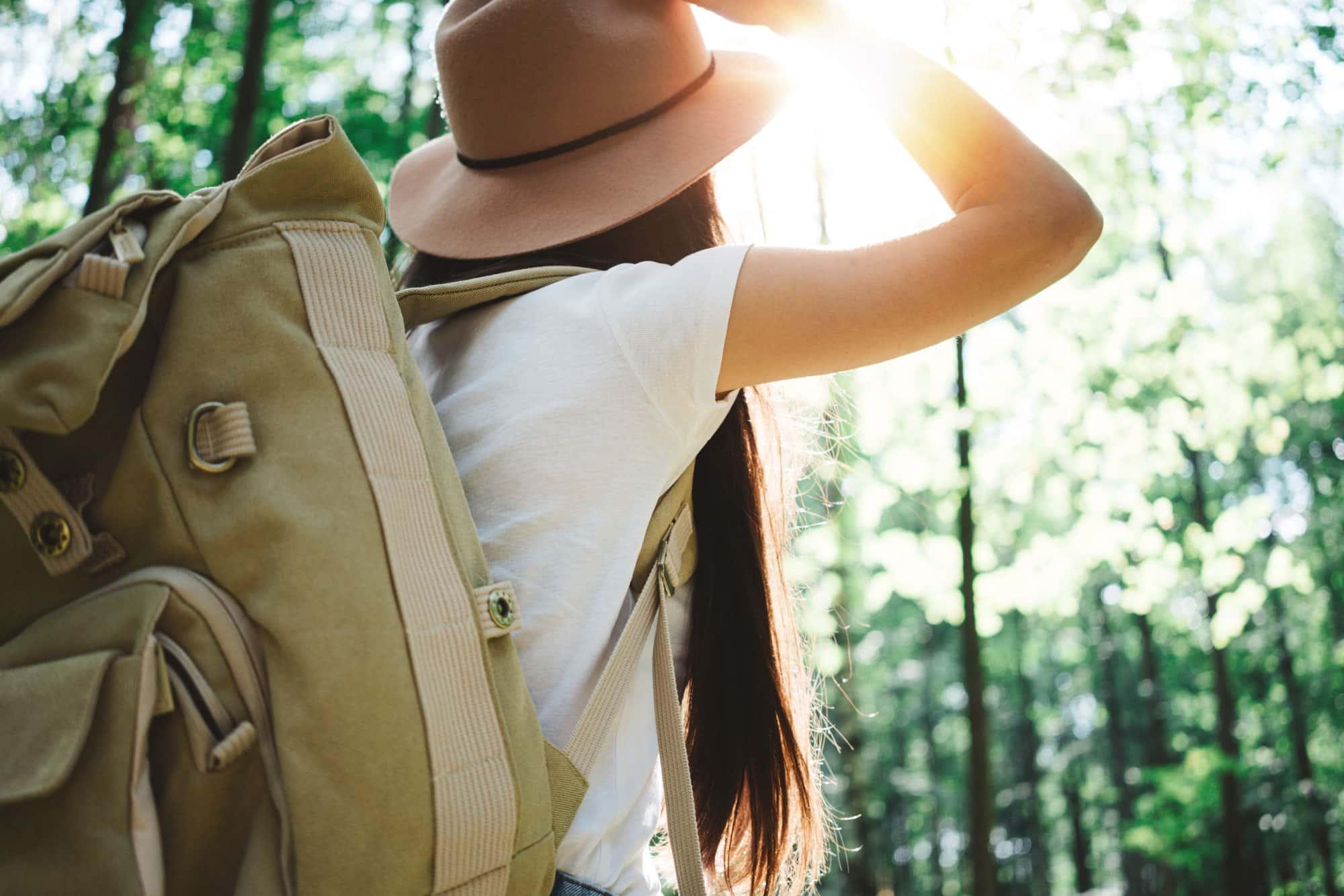 Mujer vijando sola con mochila, por el bosque