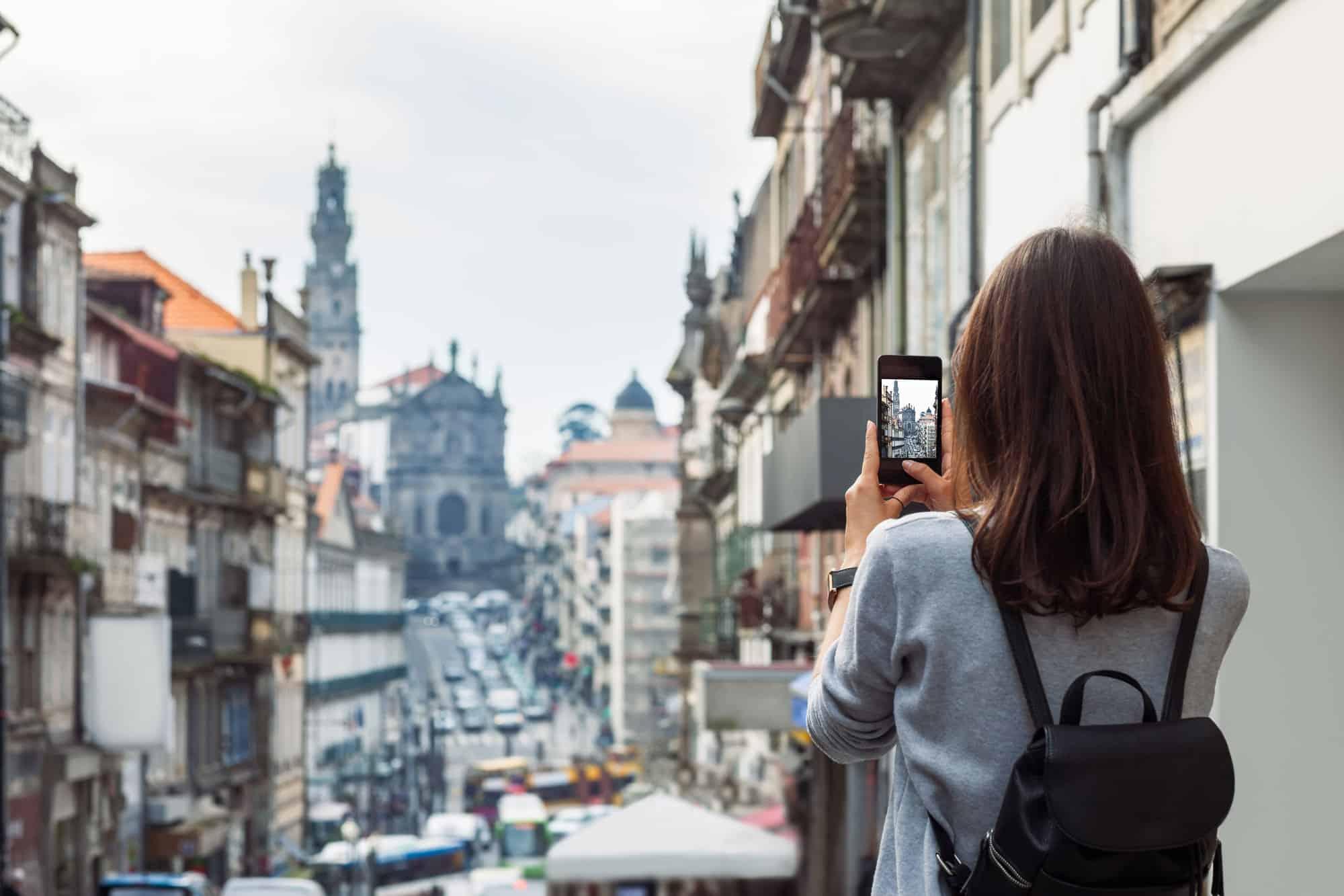 Turista hace fotos con su móvil a ciudad de Oporto en Portugal