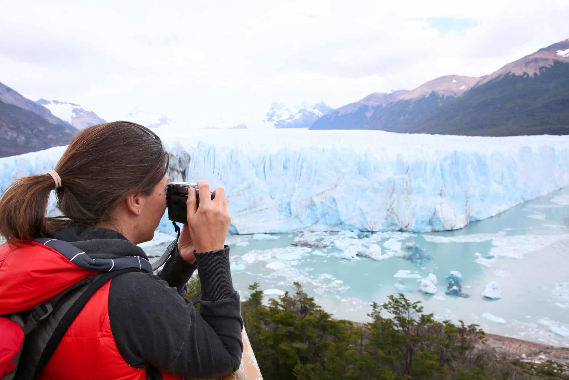 Mujer turista fotografiando glaciar de Perito Moreno en Argentina
