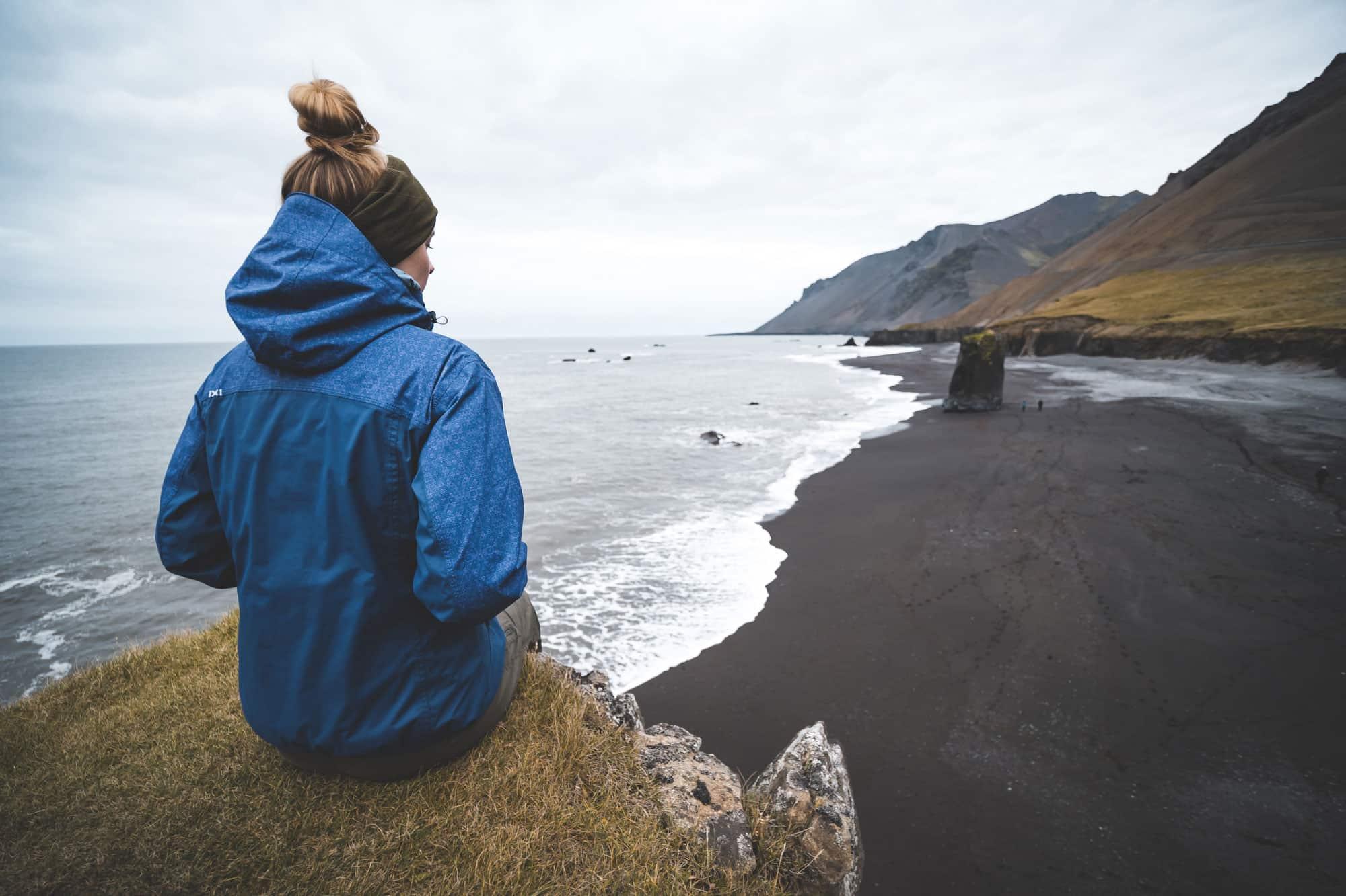 Mujer viajando sola, contempla paisaje Islandia