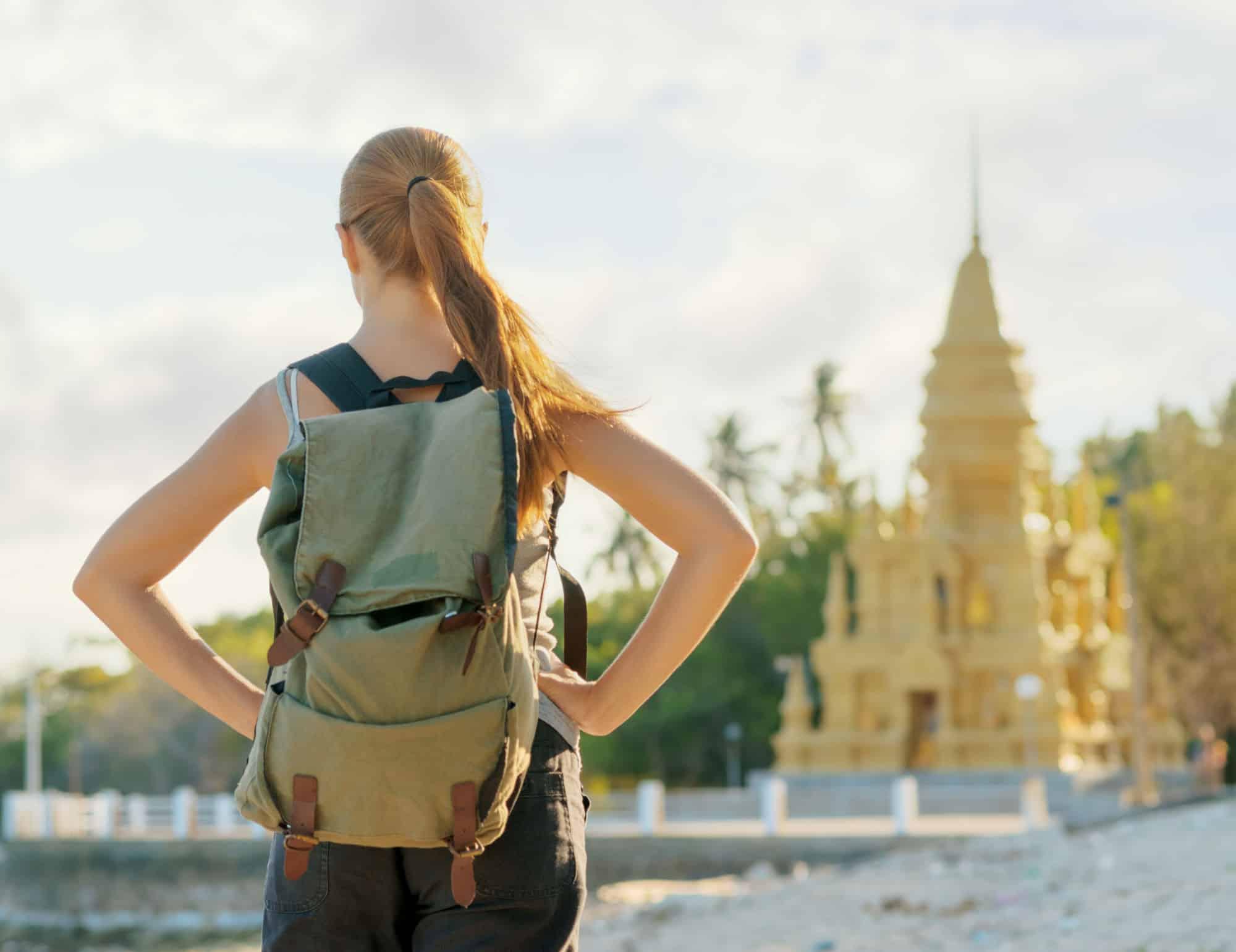 Mujer con mochila frente a una Pagoda, en Asia