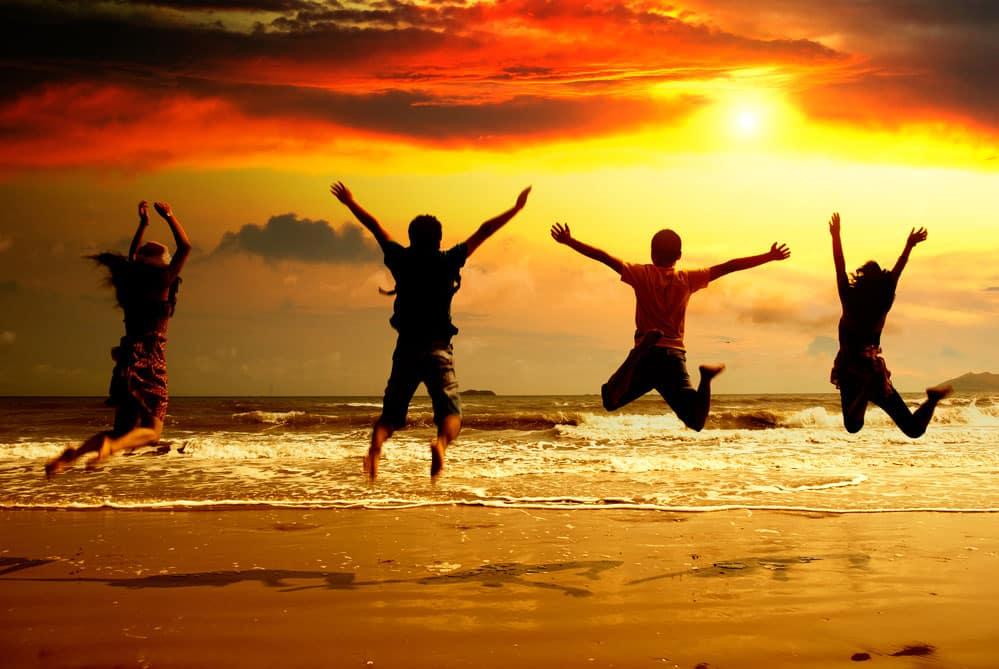 Jóvenes saltando viaje fín de curso a la playa